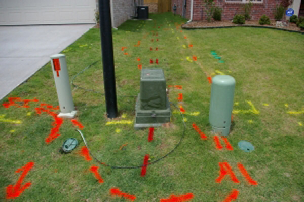 Grass is marked with red, yellow and orange utility markings.