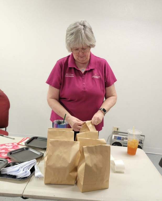Councilmember Cline bags care products for women.